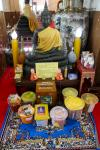 Small altar with donations in the Wihan Phramongkhon Bophit temple of Ayutthaya