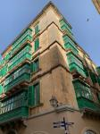 Typical Maltese house with wooden green enclosed balcony in Merchant Street of Valletta